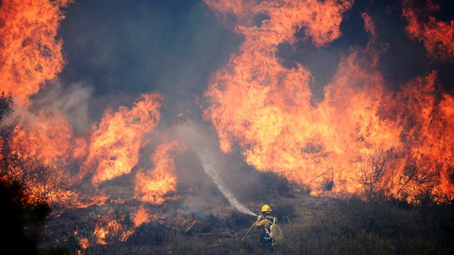 A Forestry fire fighter fights a wall of fire during an out of control wildfire, 2 May 2013 in Camarillo, California. Photo: Kevork Djansezian / Getty Images
