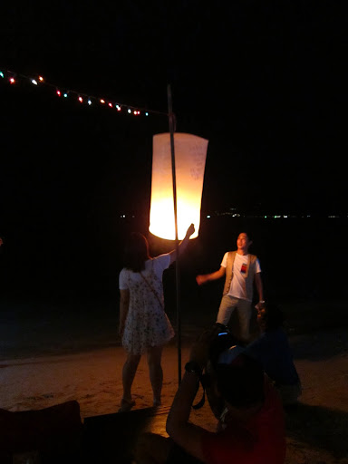 Releasing a paper lantern into the night sky.