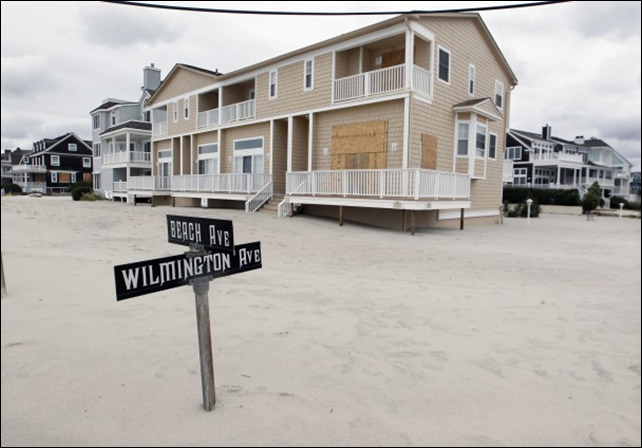 A street sign is buried in sand in Cape May, N.J., after Hurricane Sandy passed through the area, 30 October 2012. Photo: Mel Evans / AP