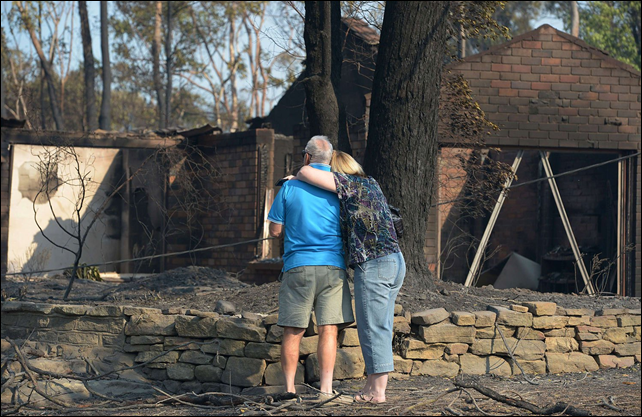 A couple look at their house burnt out by bushfires in Winmalee in Sydney's Blue Mountains, on 18 October 2013. Photo: Greg Wood / AFP / Getty Images