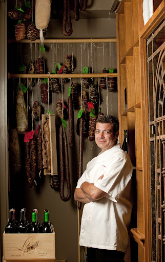 Chef Spencer Minch of Emeril's Delmonico stands among beautiful aged meats and wines.