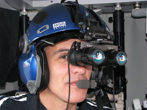 Flight nurse Jim Lawrence demonstrates how the night vision goggles fit onto the helmets already worn by the flight crew during flight.