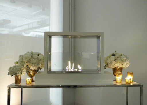 Gorgeous arrangements flanked the Taylor Creative fireplace in a lounge.