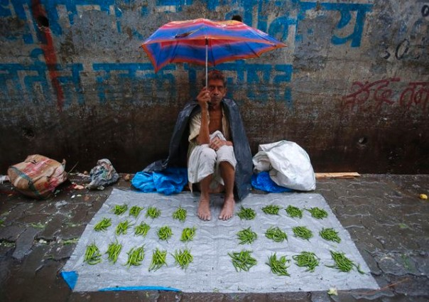 A vendor sells vegetables at a market during monsoon rains in Mumbai, on 18 June 2013. The rains are at least twice as heavy as usual in northwest and central India as the June-September monsoon spreads north, covering the whole country a month earlier than normal. Photo: Vivek Prakash / REUTERS