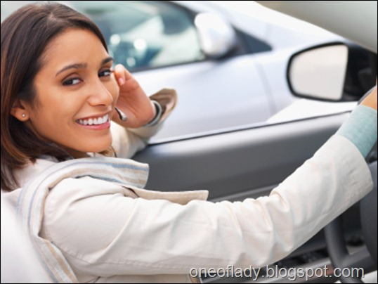 Happy hispanic woman talking mobile phone in car