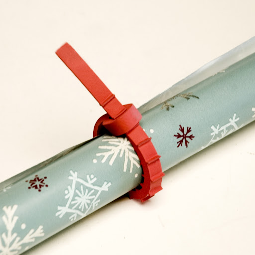 To keep wrapping paper rolls from unraveling, the Q Knot works better than a piece of tape or a rubber band.  You control the amount of pressure applied and it comes off clean.