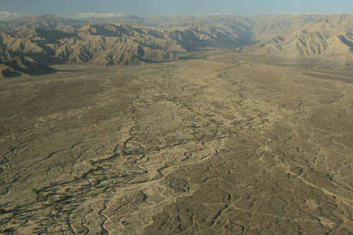 Where the arid desert meets the mountains, but in these dried out deltas there is vegetation that hints at wetter seasons.