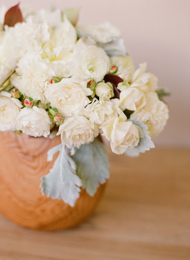 This sweet floral arrangement sits in a wood bowl. It's a great way to tie in the natural materials of the cake stand.