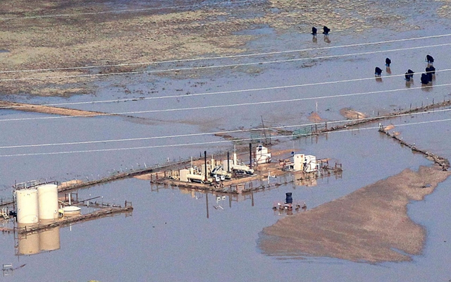 An oil storage tank on a well pad lies toppled by floodwaters in Weld County, 18 September 2013. Environmental activists have raised concerns about leaks of gas, oil and hazardous materials from compromised infrastructure. Photo: Rick Wilking / Reuters
