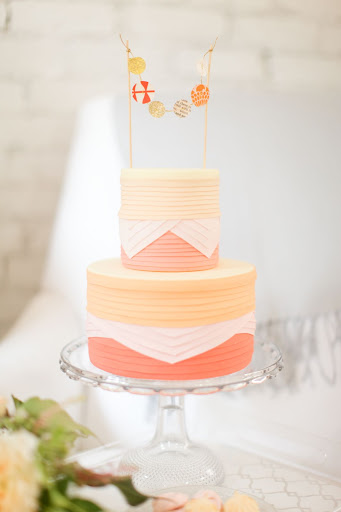 A pleated cake is topped with a small garland of its own.