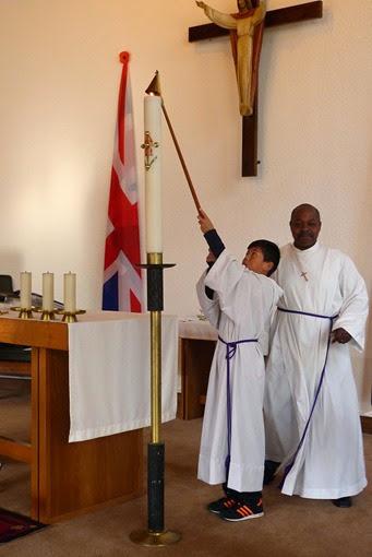 Служка пытается загасить свечу в церкви