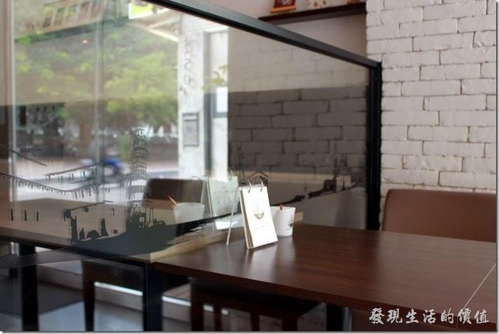 台南-綠帕克咖啡館。桌子與桌子間的隔牆則巧妙的利用後玻璃並貼上許多黑色的景物剪影,讓桌與桌之間有點距離又沒有距離。