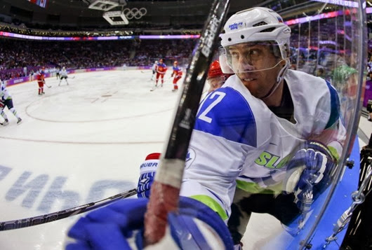 Slovenia forward David Rodman is checked up against the boards in the first period against Russia during a men's ice hockey game at the 2014 Winter Olympics, Thursday, Feb. 13, 2014, in Sochi, Russia. (AP Photo/Julio Cortez) ORG XMIT: OLYMH147