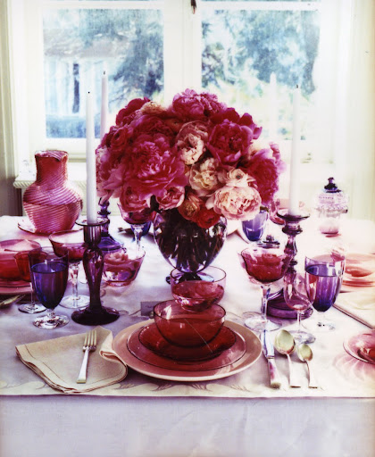 A hundi shade throws a rosy cranberry glow over mismatched pieces spanning a century of glassmaking. (Martha Stewart Living)