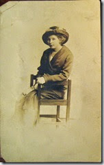 MILNE_Irene_sitting in a chair wearing a hat_enhanced
