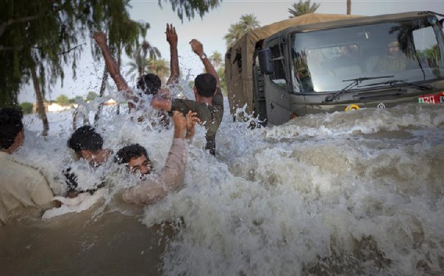 Evacuees from a flooded village dodge an army truck carrying relief supplies in Pakistan's Punjab province on 11 August 2010. Adrees Latif via Ethiopian Review