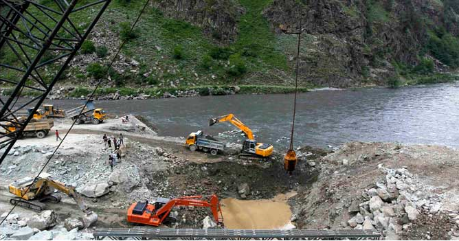 A private vehicle crosses a bridge as excavators are used at the dam site of Kishanganga power project in Gurez, 160 km north of Srinagar, 21 June 2012. Reuters