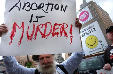 Man hold sign reading 'Abortion is MURDER'