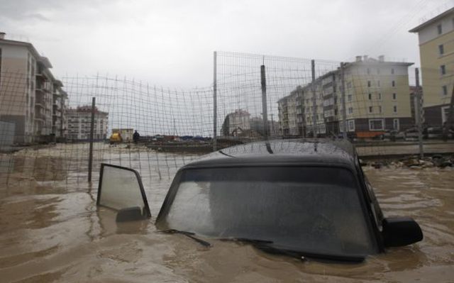A stranded vehicle drifting in floodwaters in Sochi, where a state of emergency has been declared by authorities after days of rain and mudslides, 26 September 2013. Photo: Maxim Shemetov / Reuters