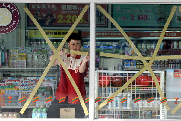 A worker tapes the window of a convenience store in Hualien, Taiwan province, on 22 August 2012, in preparation for Typhoon Tembin. China Daily