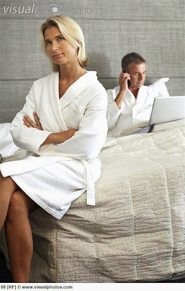 couple_sitting_on_hotel_bed_in_bathrobes_man_using_laptop_and_mobile_phone_woman_looking_bored_88.jpg