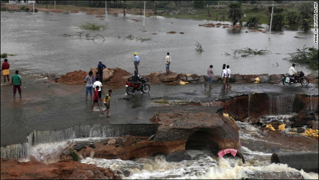 People wade through a flood-damaged road on the outskirts of Hyderabad on 26 October 2013. Photo: Mahesh Kumar A / AP