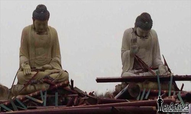 Two Buddha statues appear with their heads hung low on Tuesday, after Typhoon Usagi ravaged through Lufeng, Guangdong Province, on 23 September 2013. Photo: swsm.net