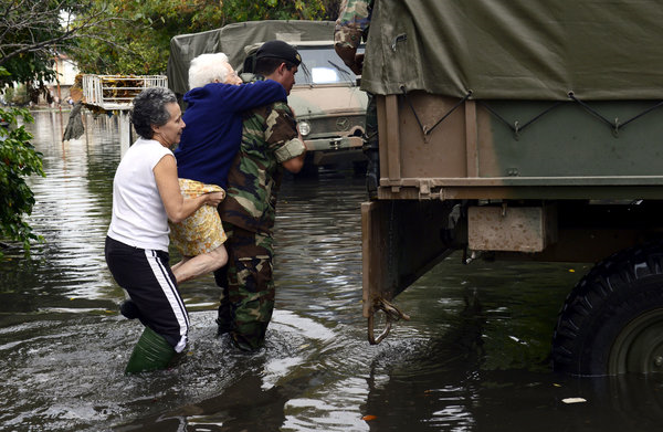 A soldier evacuates an elderly woman in a flooded street in La Plata, a provincial capital 30 miles from Buenos Aires, 3 April 2013. Photo: Daniel Garcia / Agence France-Presse / Getty Images