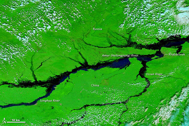 NASA's Terra satellite acquired this image of the flooded Amur (Heilongjiang) River and its tributaries in northeast China and southeast Russia. 31 August 2012. The false color images include infrared light to differentiate between muddy water and land. (The true color view shows thick sediment mixing with the river water.) Plant-covered areas are bright green, water is black and dark blue, and clouds are pale blue and white. Photo: LANCE/EOSDIS MODIS Rapid Response Team / NASA GSFC