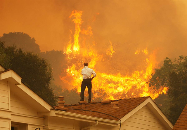 A man looks at approaching flames as the Springs Fire continues to grow on 3 May 2013, near Camarillo, California. The wildfire spread to more than 18,000 acres on day two and was only 20 percent contained Friday evening. Photo: NBC News