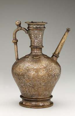 Ewer | Origin:  Syria | Period: June-July 1232  Qasim ibn Ali,Ayyubid period | Details:  Unlike most thirteenth century metalwares from Syria decorated with figural themes, this large and elegant ewer is only embellished with floral motifs and inscriptions. The unusual choice of decoration may reflect the particular taste of the patron, whose name appears on the ewer. He was Shihab al-Din Tughrul, a Turkish commander who served as regent in Aleppo in northern Syria on behalf of Sultan al-Malik al-Aziz (reigned 1216-37) of the Ayyubid dynasty. The ewer was probably reserved for religious ablution rites for which non-representational decoration was considered more appropriate. | Type: Brass with silver inlay | Size: H: 36.7  W: 21.3   D: 21.3  cm | Museum Code: F1955.22 | Photograph and description taken from Freer and the Sackler (Smithsonian) Museums.