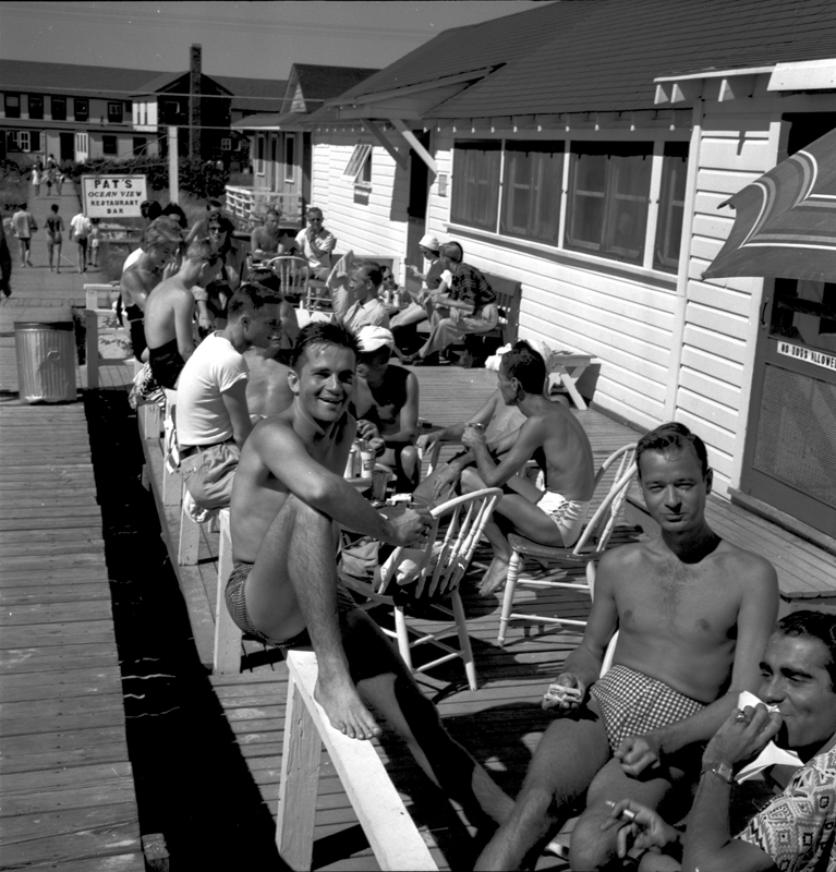 Men socialize by the seashore in Cherry Grove. August 1952.
