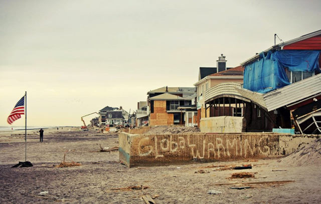 Beachfront homes in the Rockaways, New York destroyed by Hurricane Sandy. Graffiti on a bare foundation reads 'Global Warming'. Photo: Jenna Pope