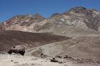 Au premier plan, un rocher. Plus loin des cailloux, des graviers et au fond, des montagnes.