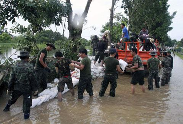 Thai soldiers pile up sandbags to make a flood barrier in Pathumthani province, central Thailand, 11 October 2011. AP