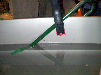 Holding the pickup tube up high to minimize flooding when the siphon fails.
