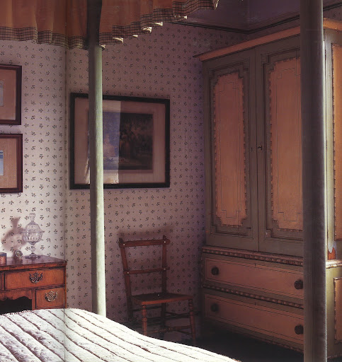 From a quintessential English bed-and-breakfast, the painted wardrobe, cane chair, sweetly patterned wallpaper and four-poster bed work so well together.