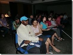 Pessoas com deficiência visual, no escurinho do cinema, assistindo ao filme Náufrago