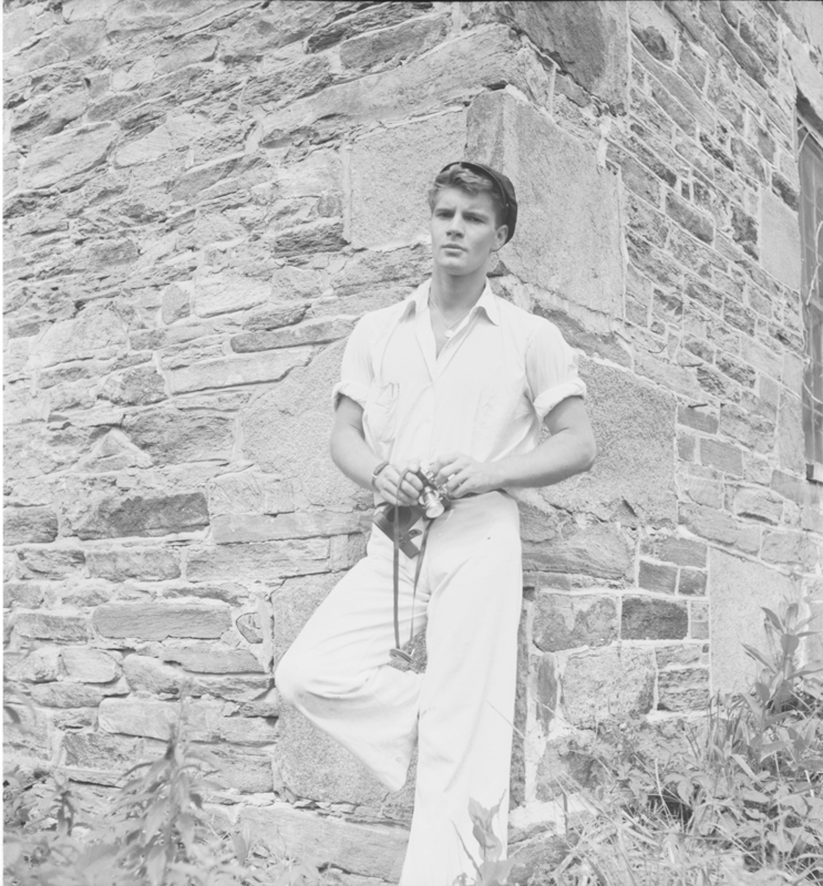 Model Christian William (Bill) Miller poses with his camera against the outside wall of the Sunstone Estate in Reading, Vermont. Miller took extensive photographs of his travels and social life from the 1940s to 1960s. August 1945.