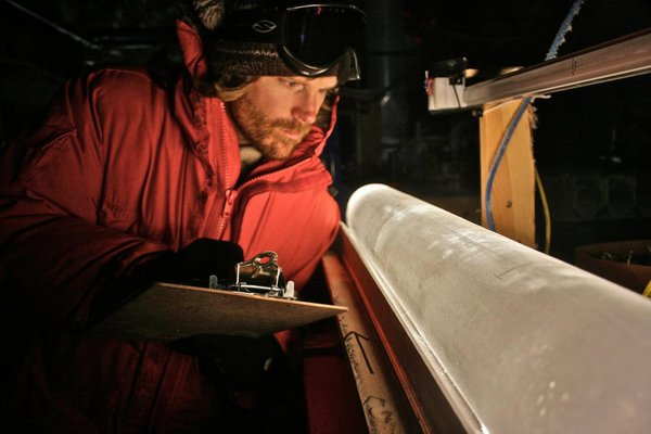 Scientist Brian Bencivengo of the National Ice Core Laboratory examines an ice core from the West Antarctic Ice Sheet. Samples from these cores provide information about past air temperatures at the location from which the core was obtained. Photo: Thomas Bauska / Oregon State University