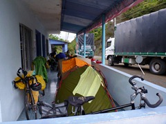 Five cyclists with three tents in a restaurant entrance.