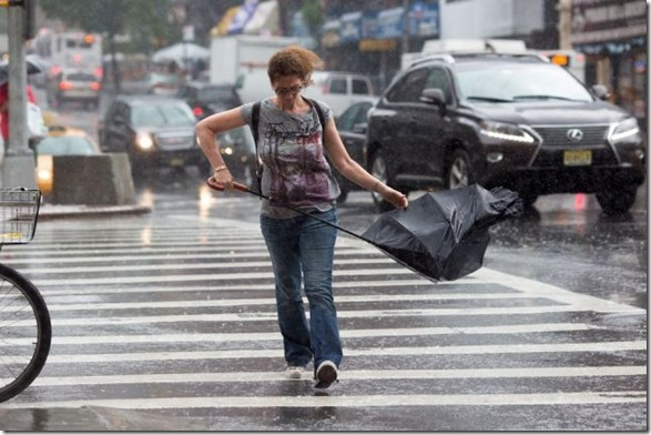 A Pedestrian finds her umbrella to be of little use while crossing Broadway at West 96th Street during a downpour on the Upper West Side, Manhattan, N.Y., Monday, June 10, 2013. Periods of rain are in forecast for the upcoming days. Credit: Claudio Papapietro for The Wall Street Journal