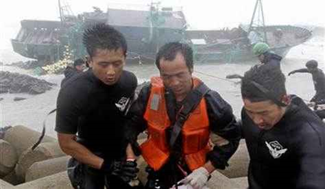 A Chinese fisherman wearing an orange life vest, center, is rescued by South Korean coast guard officers from a Chinese ship in Jeju, South Korea, Tuesday, 28 August 2012. Typhoon Bolaven pounded South Korea with strong winds and heavy rain Tuesday, while the nation's coast guard battled rough seas in a race to rescue fishermen on two Chinese ships that slammed into rocks off the southern coast.  Kim Ho-chun / AP Photo / Yonhap