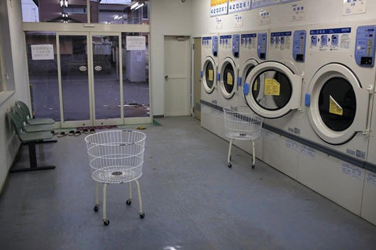 Inside the twenty kilometre Exclusion Zone surrounding the Fukushima Daiichi nuclear plant.<br /><br />An abandoned laundromat on the main street in Odaka, where all the residents were forced to leave on a moments notice, leaving everything behind. While the town has virtually no electricity or water, some of the homes and businesses still do, like this laundromat.<br /><br />Photograph by Donald Weber/VII Network
