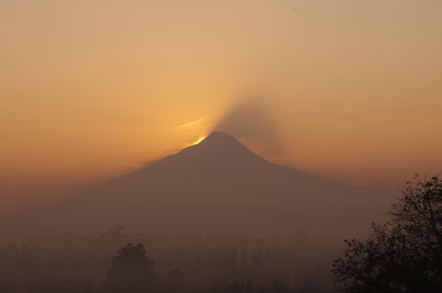 Sunrise over Mount Merapi as seen from Borobudor. Indonesia's most active volcano.
