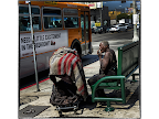 Homeless woman on the street with passing bus, Los Angeles. <em>© Margo Berdeshevsky</em>