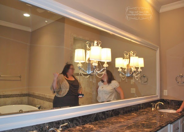 Long horizontal builder mirror framed with light fixtures on mirror