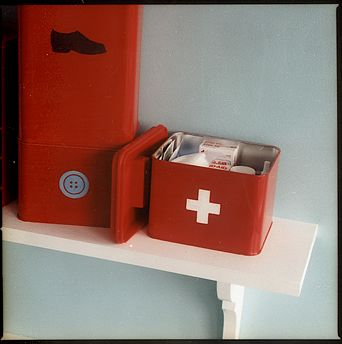 I really love this idea for making your own first-aid kit container and other types of kits too.  Paint metal kitchen canisters, easily found at tag sales, and then designate them with an icon to indicate their contents.  One for shoe care, one for sewing repairs and one for first-aid.