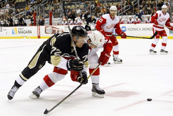 Sep 22, 2014; Pittsburgh, PA, USA; Pittsburgh Penguins right wing Patric Hornqvist (72) chases the puck as Detroit Red Wings defenseman Alexei Marchenko (47) defends during the third period at the CONSOL Energy Center. The Red Wings won 2-1. Mandatory Credit: Charles LeClaire-USA TODAY Sports
