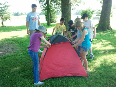 Campers put the finishing touches on a tent they put together as a team while County Council Matt Romoser supervises.  Photo courtesy of the Washington County Extension.
